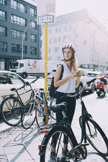 Full length of businesswoman standing with bicycle on street in city