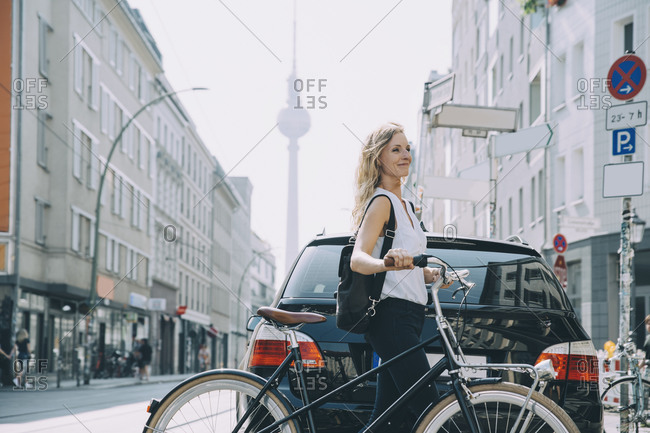 Smiling young woman with backpack riding bicycle on street in city