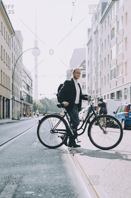 Full length of businessman with bicycle on road in city