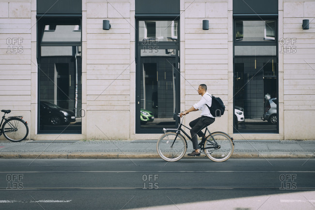 Full length of businessman riding bicycle on street against building in city