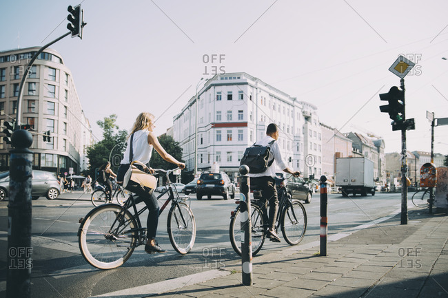 Full length of male and female entrepreneurs riding bicycle on road in city
