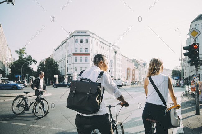 Rear view of male and female colleagues standing with bicycle on road in city