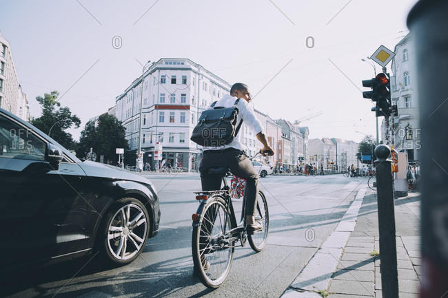 Full length of male entrepreneur riding bicycle on road in city against sky