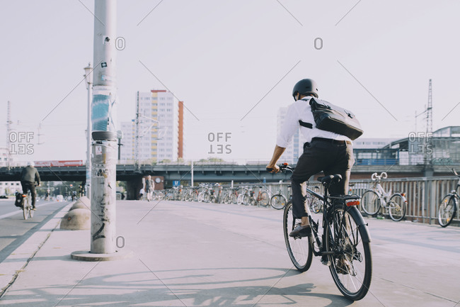 Rear view of businessman riding bicycle on sidewalk against clear sky in city