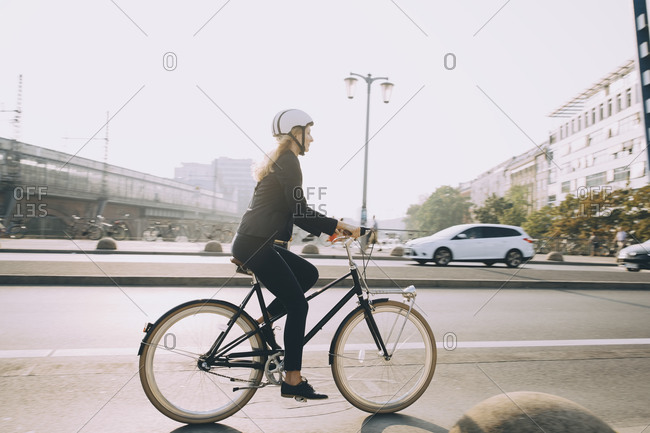 Full length of female executive wearing helmet riding bicycle on road in city