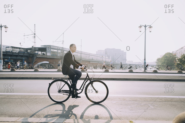 Side view of male entrepreneur riding bicycle on city street against sky