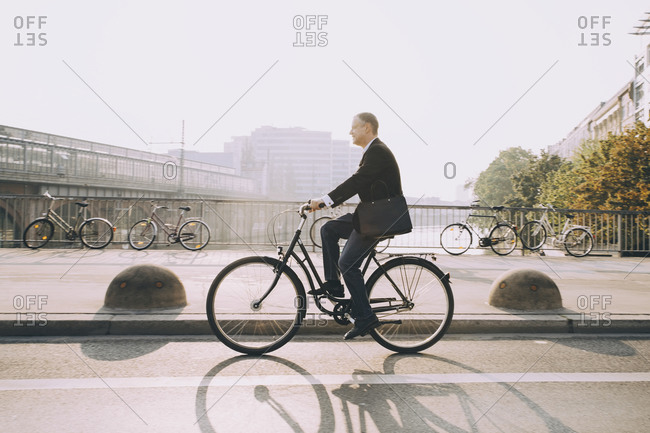 Side view of businessman riding bicycle on road in city against sky