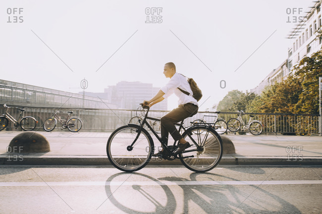 Full length of businessman riding bicycle on street in city against sky