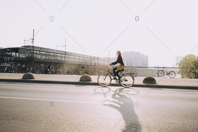 Female entrepreneur riding bicycle on street in city against sky