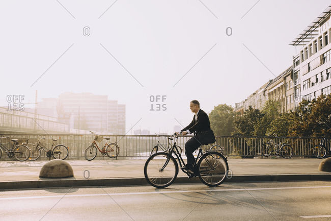Full length of mature man riding bicycle on road in city against sky