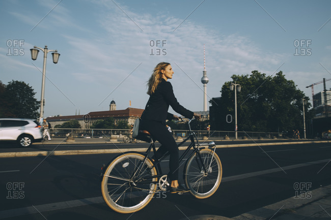 Side view of businesswoman riding bicycle on street in city