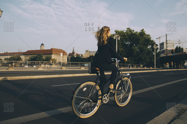 Rare view of female executive riding bicycle on road in city against sky