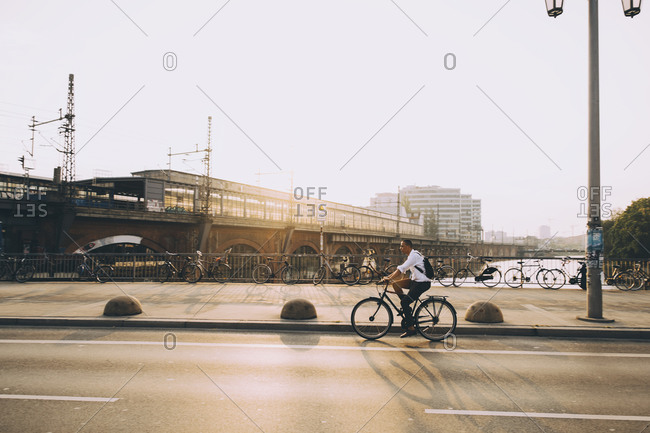 Side view of male executive riding bicycle on street in city against sky