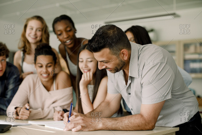 Smiling tutor teaching teenage students while leaning over table in classroom