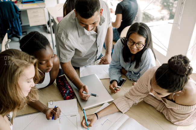 High angle view of teenagers studying while professor standing by table in classroom