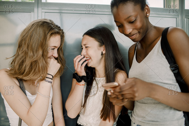 Cheerful junior high students with friend using smart phone while standing in school corridor