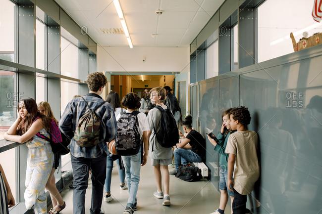 Rear view of students walking in school corridor