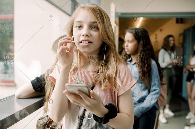 Female student talking through in-ear headphones in school corridor