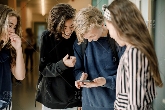 Smiling male students using smart phone while standing by female friends in school corridor
