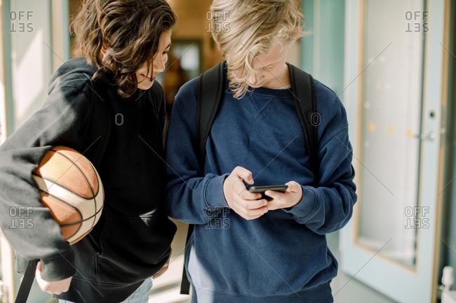Male students using smart phone in school corridor