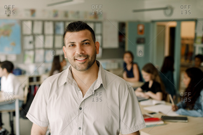 Portrait of smiling male teacher standing in classroom