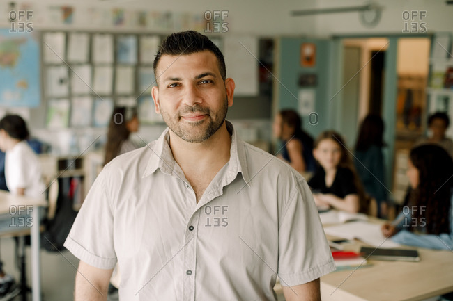 Portrait of smiling male tutor standing in classroom