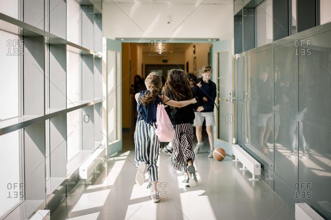Rear view of female friends running in school corridor