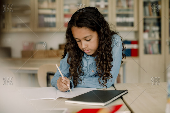 Student writing in book while sitting by table in classroom