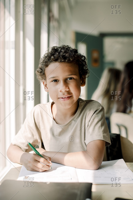 Portrait of male student studying in classroom