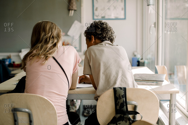 Rear view of male and female students studying together in classroom