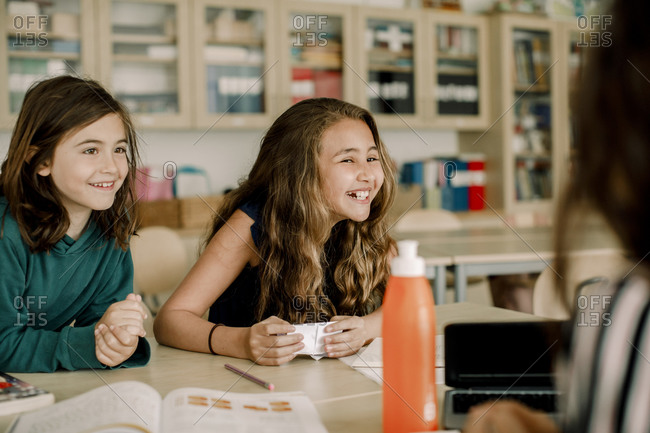 Smiling female student with paper sitting by friend in classroom