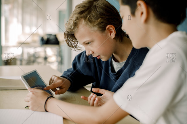 Male student pointing at digital tablet while sitting with friend in classroom