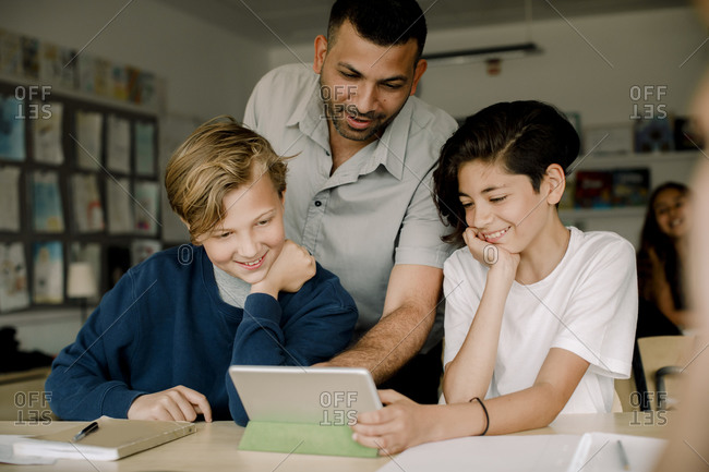 Smiling male tutor with students using digital tablet while sitting in classroom