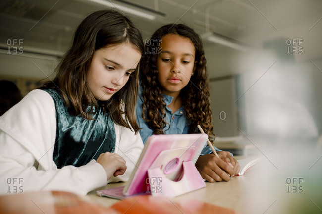 Female students using digital tablet at table in classroom