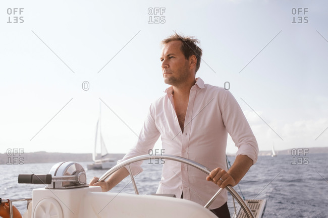 Confident mature man sailing catamaran with helm on sea against sky