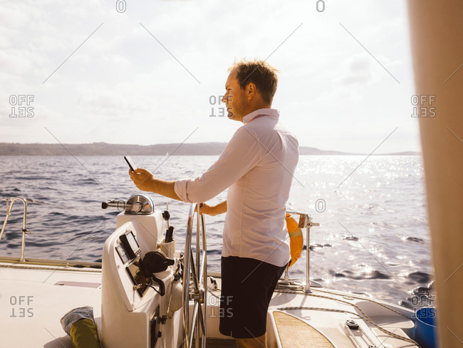 Side view of man holding mobile phone while sailing catamaran on sea against sky during sunny day