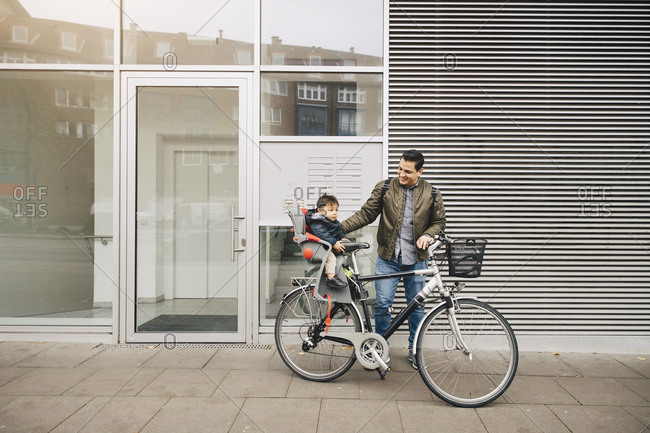 Smiling father riding bicycle with son sitting in safety seat on sidewalk in city
