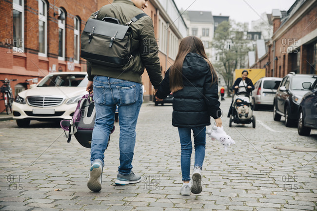 Rear view of father and daughter holding hands walking on footpath in city
