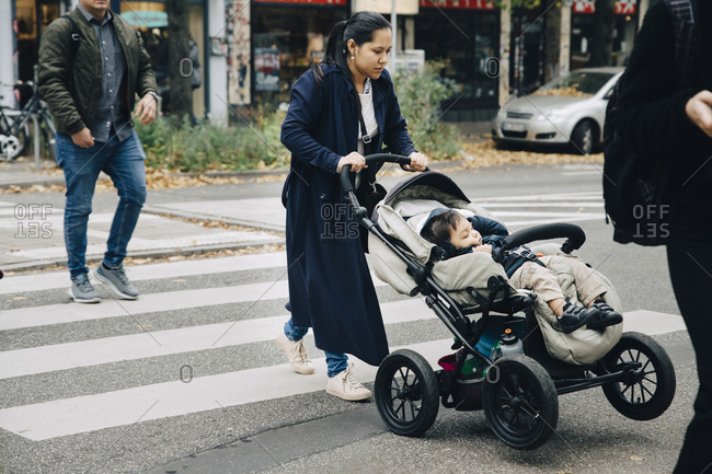 Full length of mother with son sitting in stroller crossing road in city