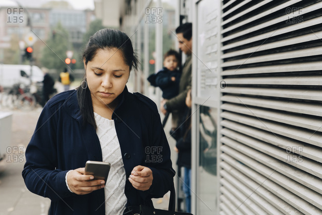 Mid adult woman using mobile phone while walking on sidewalk in city