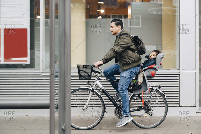Full length of father riding bicycle with son on sidewalk in city