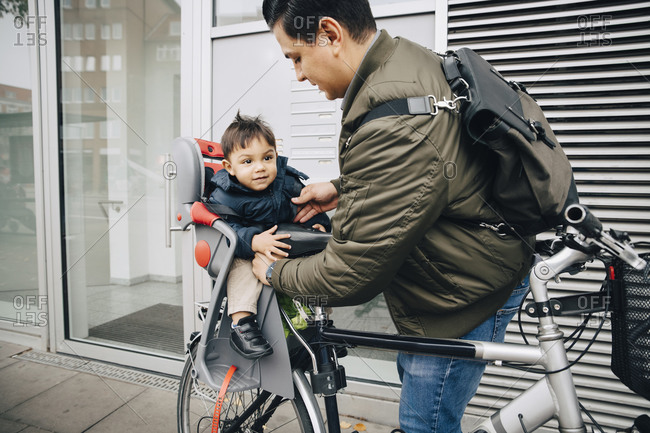 Father holding son sitting in safety seat of bicycle on sidewalk in city