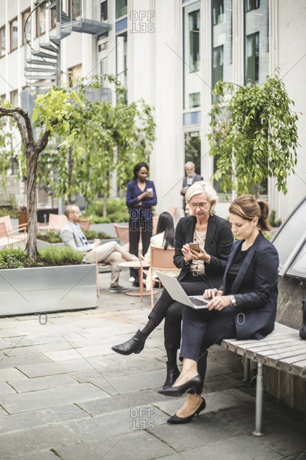 Full length of businesswomen using laptop while sitting on bench with colleagues in background office yard