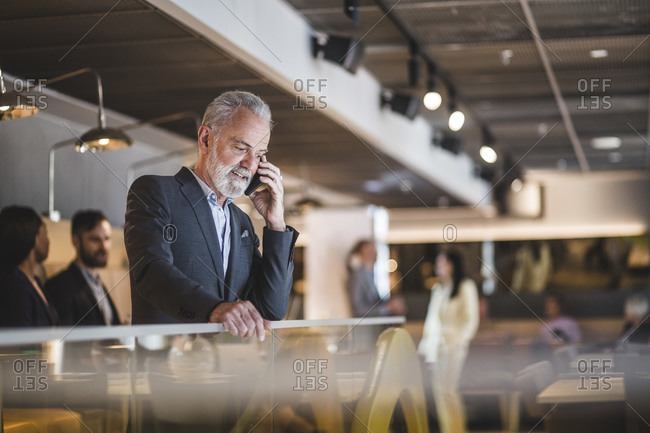 Senior male entrepreneur talking on smart phone while standing by railing in office