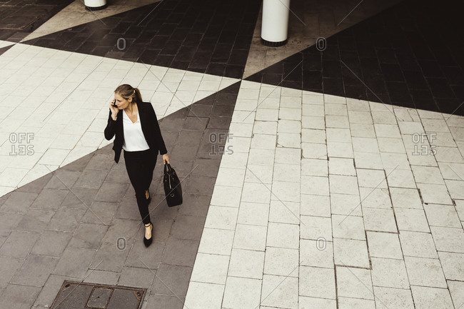 High angle view of businesswoman talking through phone while walking on street