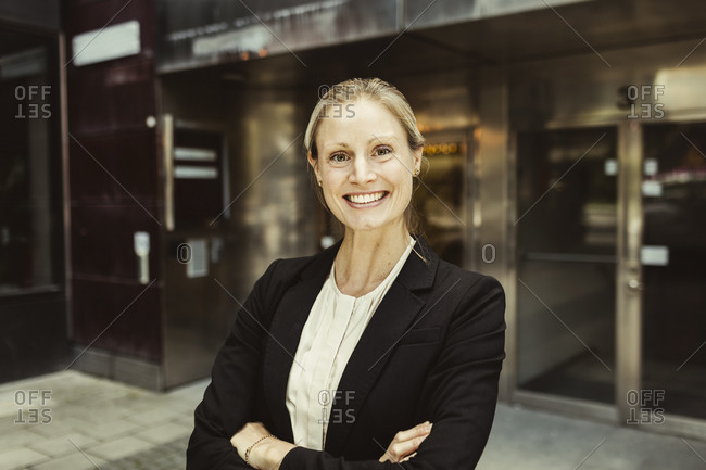 Portrait of confident female entrepreneur with arms crossed standing against building