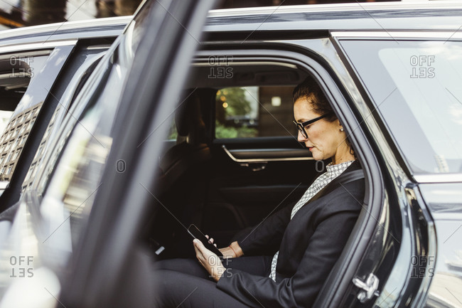 Entrepreneur using smart phone while sitting in car