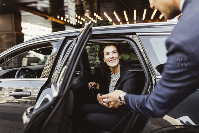 Smiling female entrepreneur looking at male coworker while sitting in car