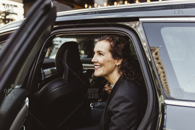 Smiling female entrepreneur looking away while exiting from car