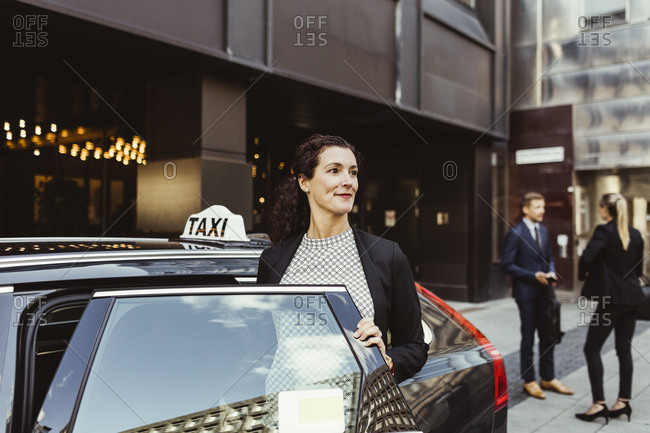 Smiling female entrepreneur looking away while entering in taxi